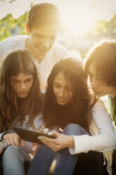 Teenagers using digital tablet together outdoors - MASF03784
