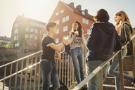 Teenagers talking while having drinks on steps in city - MASF03793