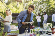 Young man holding empty plate at dining table in backyard during summer party - MASF03802