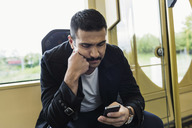 Young man text messaging through mobile phone in tram - MASF03811