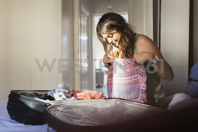Young woman trying clothes while packing for vacation in bedroom - MASF03826