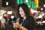Young woman laughing while using smart phone in city at night - MASF03850