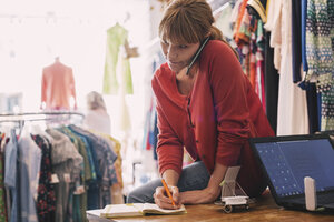 Woman writing order in diary while talking on smart phone at thrift store - MASF03856