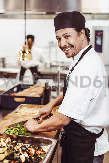 Side view portrait of happy male chef cutting leafy vegetables at commercial kitchen - MASF03865