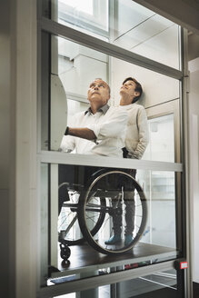 Son and father in wheelchair lift at home - MASF03877
