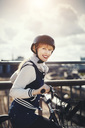 Side view portrait of happy businesswoman standing with bicycle on bridge - MASF03880