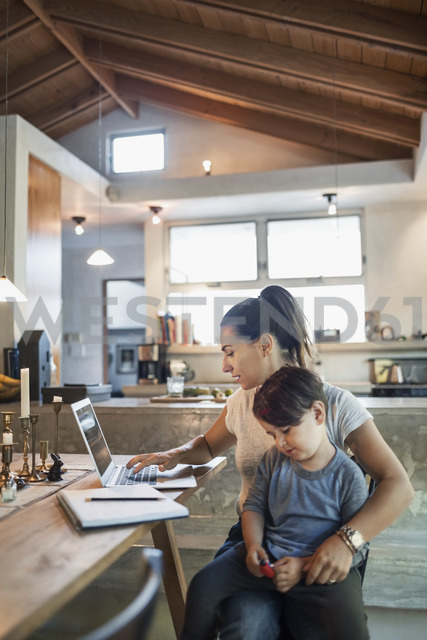 Son sitting with mother working on laptop at dining table - MASF03886
