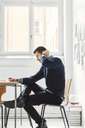 Side view of mid adult businessman writing in book at office desk - MASF03910