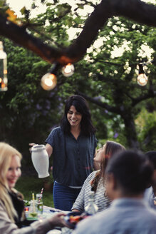 Smiling woman holding jug while friends sitting at dining table during party - MASF03916