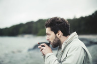 Side view of man drinking coffee at sea shore - MASF03928