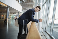 Side view of happy businessman leaning on railing at airport - MASF03940