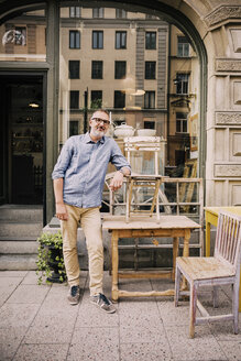 Smiling owner leaning on chair outside antique shop - MASF03952
