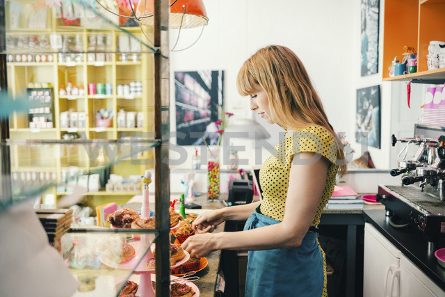 Side view of female barista with pastries at cafe counter - MASF03958
