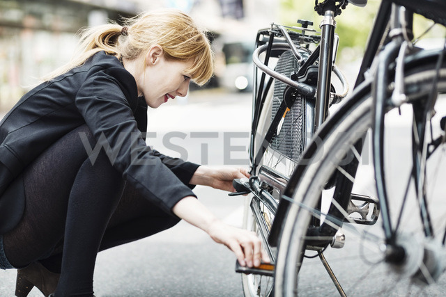Side view of businesswoman repairing bicycle on street - MASF03961