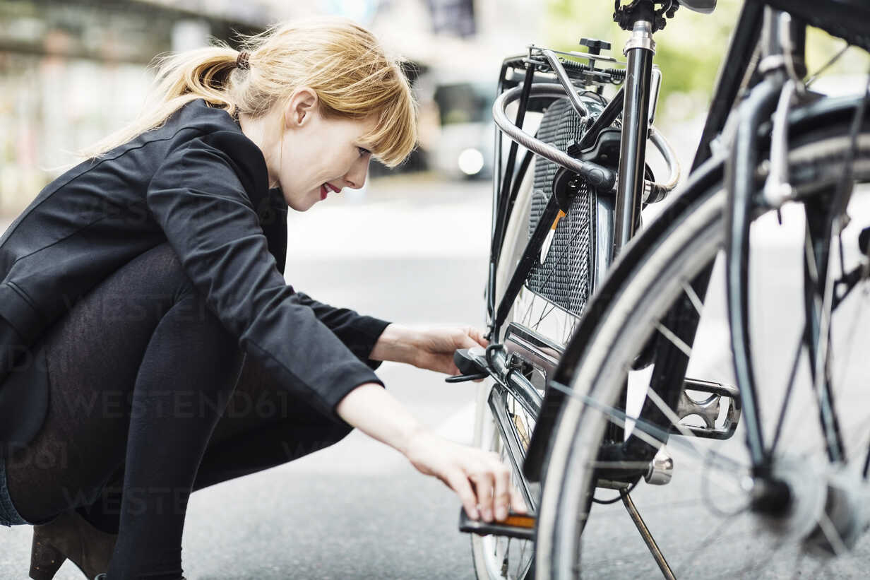 Side view of businesswoman repairing bicycle on street - MASF03961 - Maskot ./Westend61
