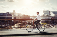 Side view of businessman riding bicycle on bridge in city - MASF03964