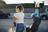 Rear view of woman holding bicycle with son sitting on back seat outdoors - MASF03979