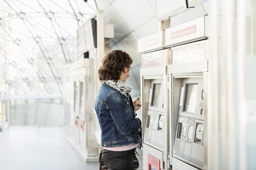 Side view of businesswoman looking at ticket machine in railway station - MASF03982