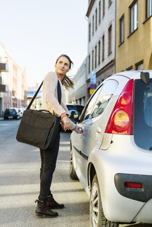 Side view of businesswoman opening car door on street - MASF03988