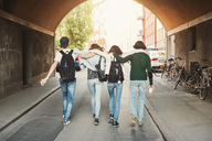 Rear view of teenagers with arms around walking in tunnel - MASF03994