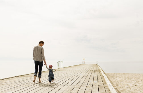 Rear view of mother and daughter walking on pier at beach against sky - MASF04009