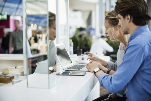Side view of business people using credit card and laptop at airport lobby - MASF04015