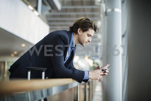Side view of businessman using mobile phone while leaning on railing at airport - MASF04018