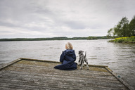 Rear view of senior woman and dog on pier at lake against cloudy sky - MASF04027