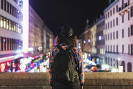 Rear view of woman carrying backpack standing on bridge in city at night - MASF04030