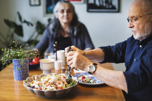 Senior man serving salad for himself while sitting with woman at table - MASF04033