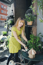 Portrait of happy owner with potted plant outside store - MASF04042