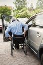 Rear view of man in wheelchair outside car - MASF04045