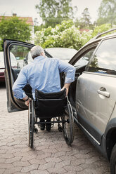 Rear view of man in wheelchair outside car - MASF04045