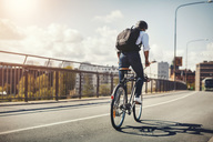Rear view of businessman riding bicycle on bridge in city - MASF04048