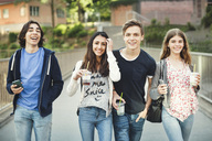 Portrait of happy teenagers holding disposable glasses and smart phones on bridge - MASF04075