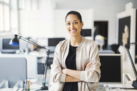 Portrait of smiling young businesswoman standing arms crossed in office - MASF04078