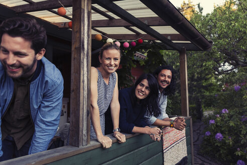 Portrait of happy young woman standing with friends on porch at log cabin - MASF04081