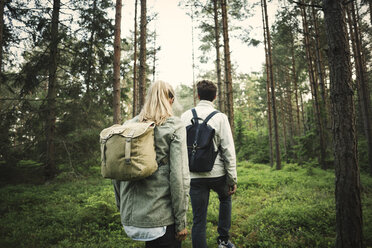 Rear view of couple carrying backpacks while walking through forest - MASF04096