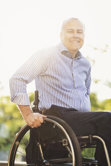 Portrait of happy man sitting in wheelchair outdoors - MASF04111