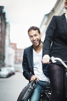 Portrait of happy businessman enjoying bicycle ride with colleague on street - MASF04114