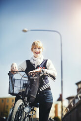 Portrait of happy businesswoman with bicycle standing against sky - MASF04117