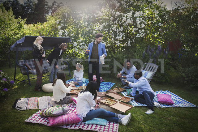 Multi-ethnic friends having snacks during summer party at yard - MASF04135