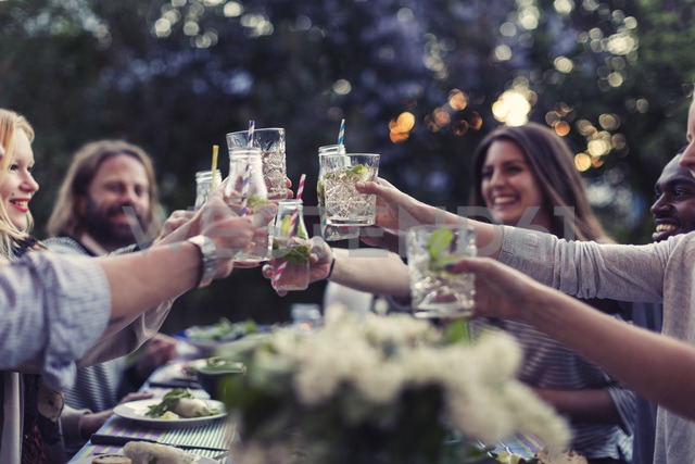 Multi-ethnic friends toasting mojito glasses at dinner table in yard - MASF04138