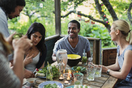 Multi-ethnic friends having food at porch in log cabin - MASF04141