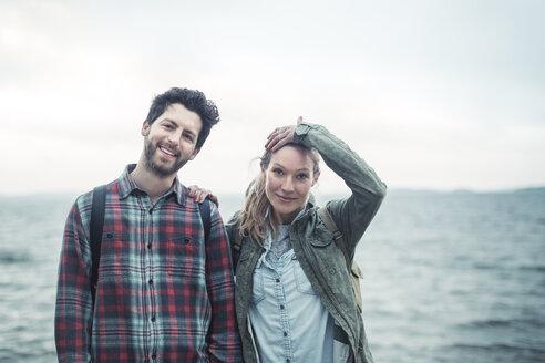 Portrait of confident wonderlust couple standing against sea - MASF04150