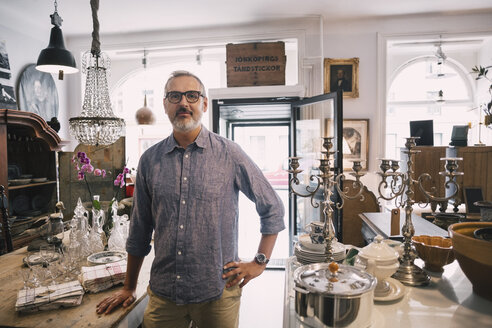 Portrait of confident owner standing with hand on hip in antique store - MASF04156
