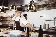 Manlig kock sträcker sig efter ingredienser i restaurangkök - MASF04162