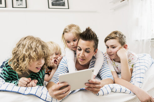 Mother and children using digital tablet lying in bed at home - MASF04177