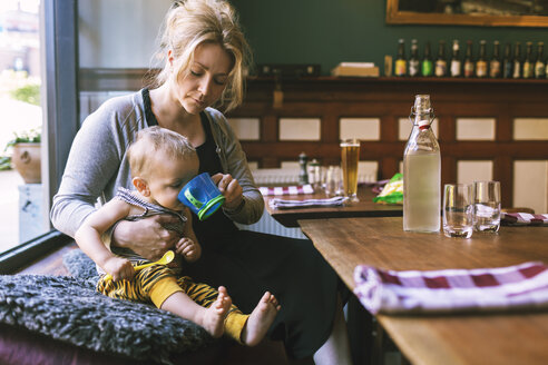 Mid adult woman feeding water to son in restaurant - MASF04192