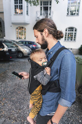 Mid adult man using mobile phone while carrying baby in carrier on sidewalk - MASF04195